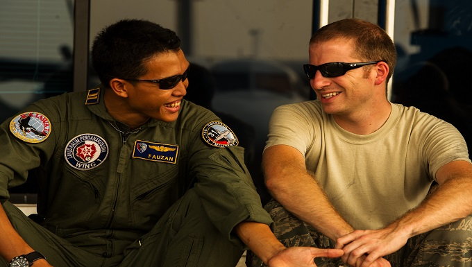 Personnel Exchange - two military men talking to each other and smiling, wearing sunglasses