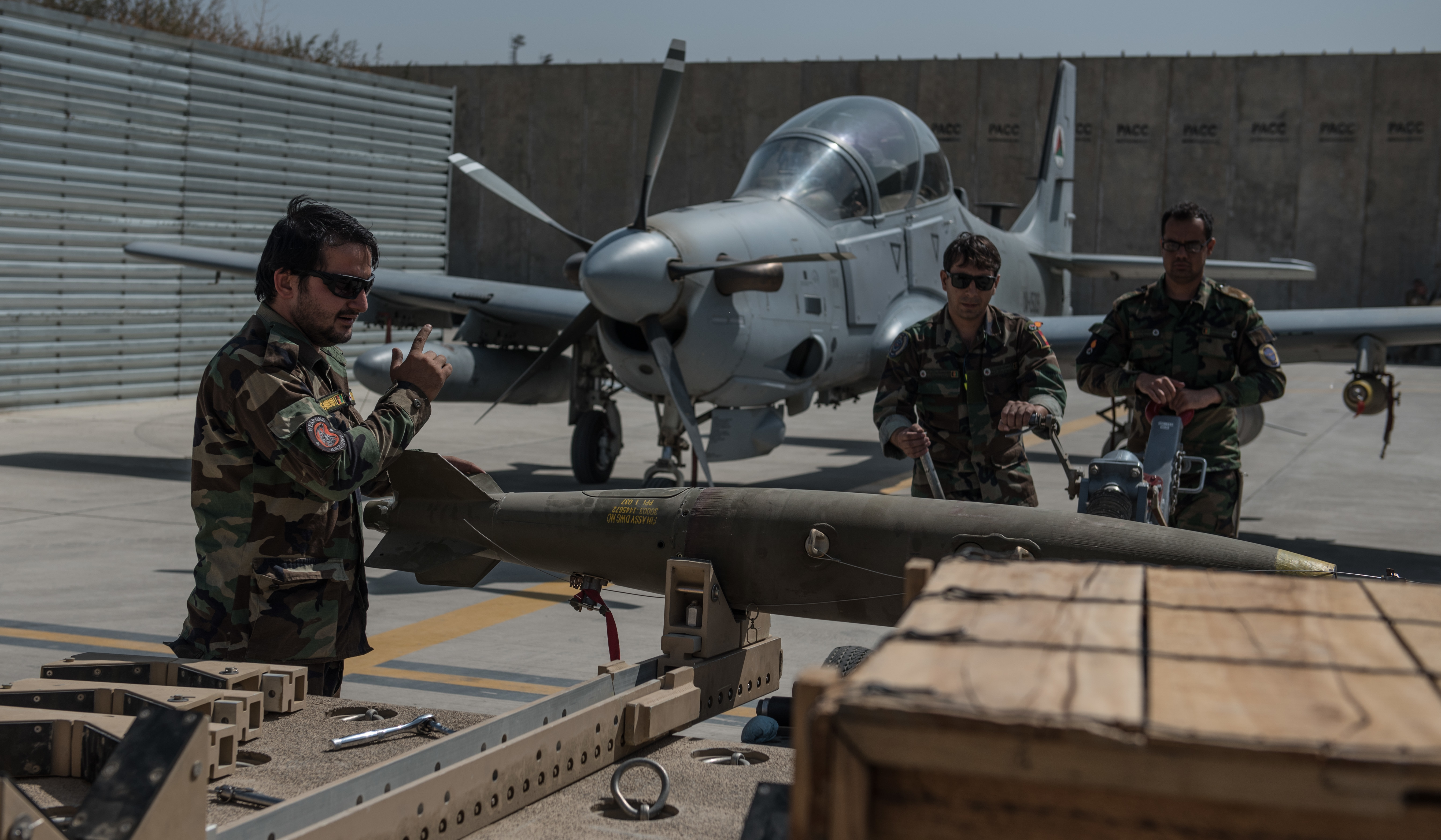 Afghan munitions Airmen move an Mark-81 bomb toward an A-29 Super Tucano Sept. 12, 2017, in Kabul, Afghanistan. Munitions crews regularly train loading procedures in order to hone and practice their skills, while also supporting active combat operations against anti-government forces throughout Afghanistan. (U.S. Air Force photo by Staff Sgt. Alexander W. Riedel)