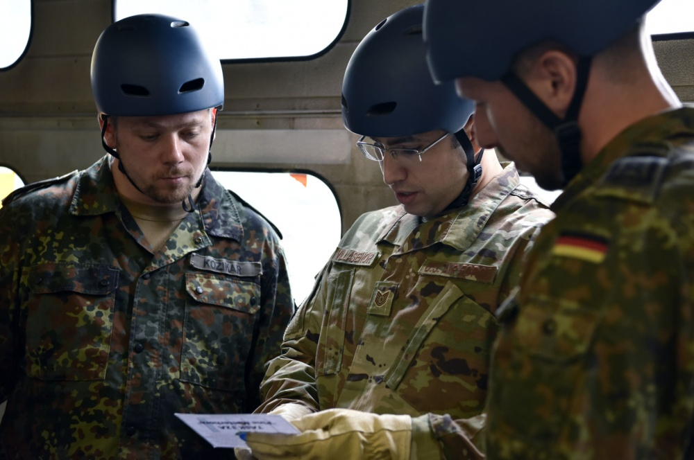 U.S. Air Force Tech. Sgt. Emmanuel Villasenor, German NCO Academy instructor, discusses a game plan with fellow instructors, German air force HptFw Simon Kozikar, left, and HptFw Jan Weber, right, before completing an obstacle within the Inter-European Air Forces Academy Project X course Sept. 24, 2019 at Kapaun Air Station, Germany. Villasenor teaches at the German NCOA as part of the U.S. Air Force Military Personnel Exchange Program. He and his German counterparts visit with the Kapaun U.S. Air Force professional military education instructors annually to share ideas and strengthen their partnership. (U.S. Air Force photo by Tech. Sgt. Lindsey Maurice)